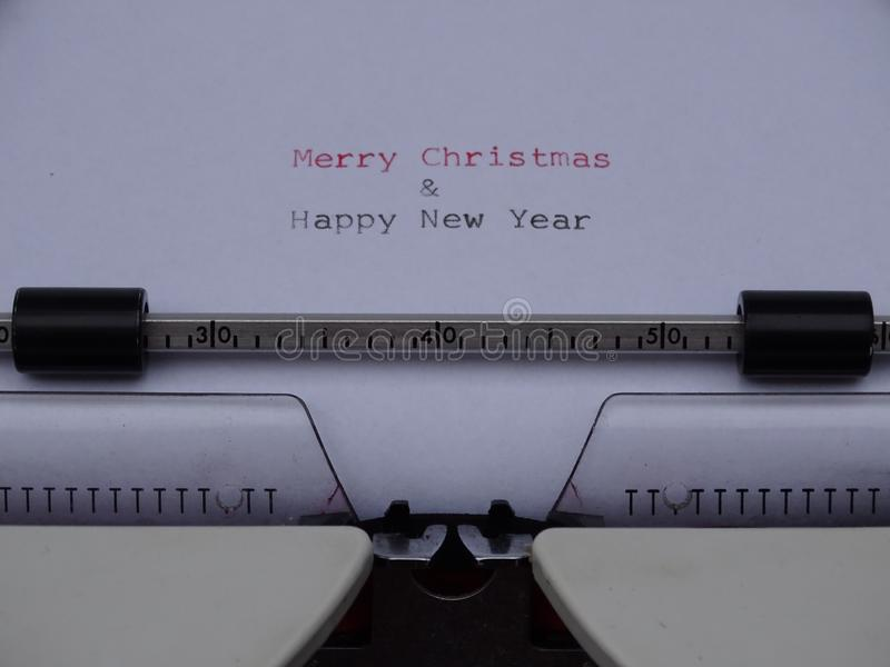 Typed Merry Christmas and Happy New Year. On elektric typemachine white papern stock photos