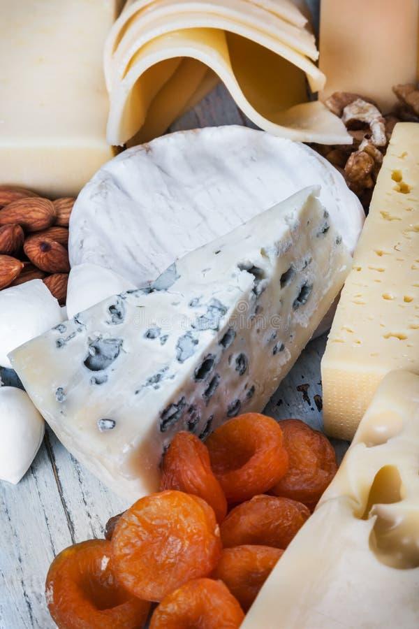 Typer av olika ostmozzarella, brun, roquefort, Maasdam etc. i tabellen royaltyfria bilder