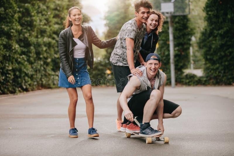 Types adolescents sur la planche à roulettes avec des filles images libres de droits