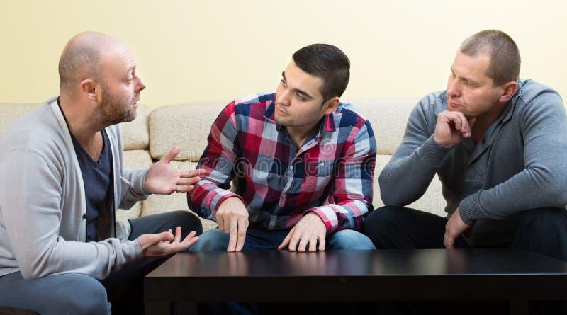 Types partageant des problèmes à la table photographie stock
