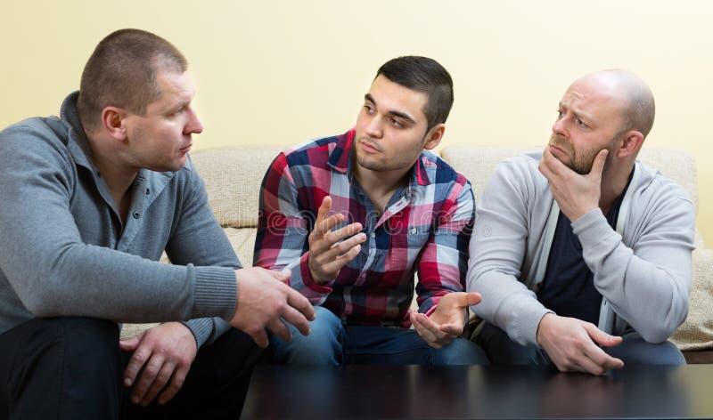 Types partageant des problèmes à la table photos stock