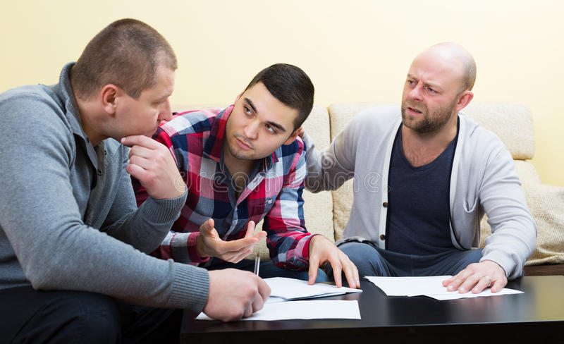 Types s'asseyant avec des papiers photo stock