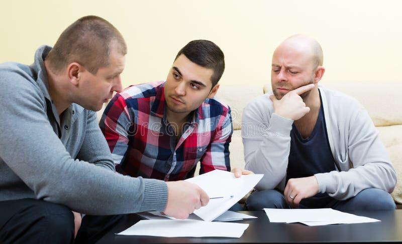 Types s'asseyant avec des papiers image stock