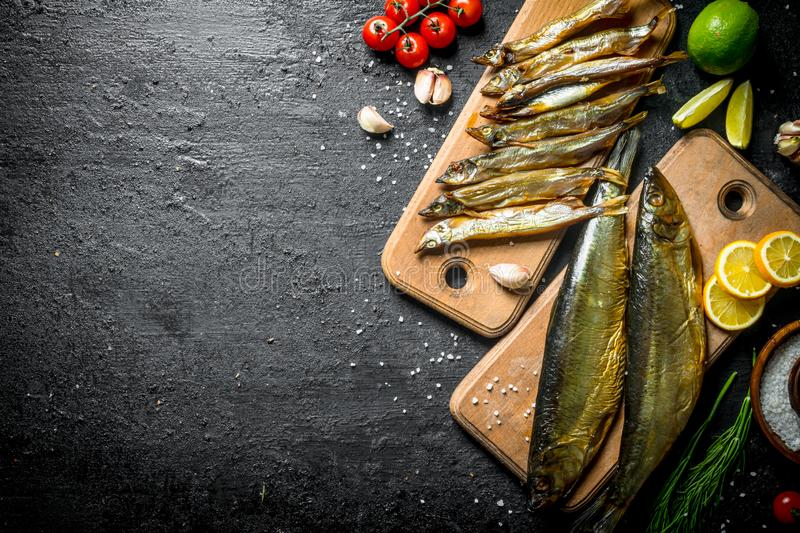 Types of smoked fish with slices of lime, lemon, tomatoes and herbs royalty free stock photography