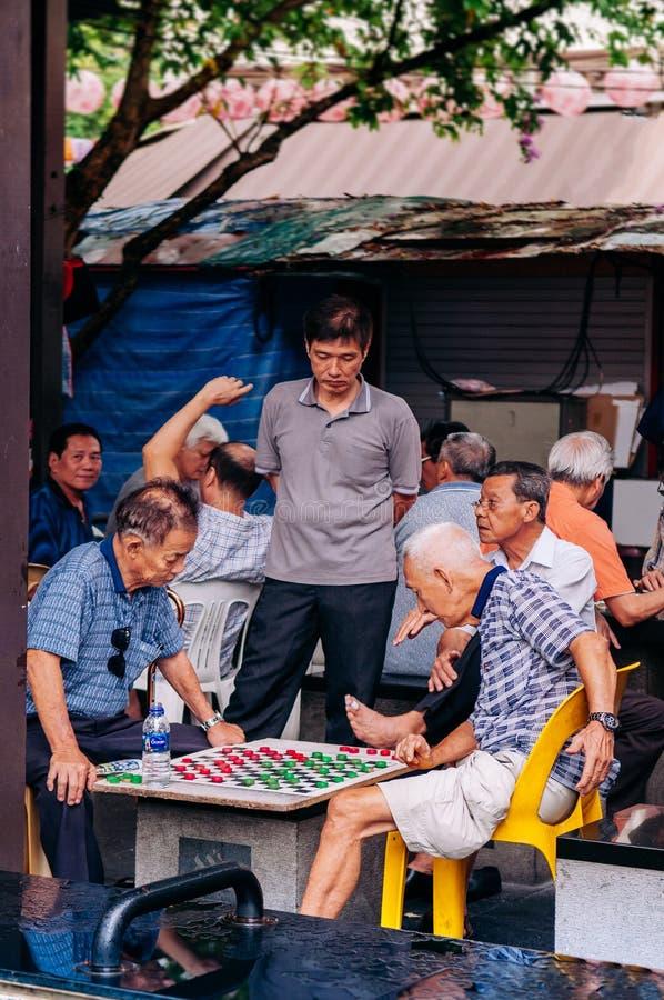 Types supérieurs asiatiques jouant aux échecs avec le groupe d'amis photos stock