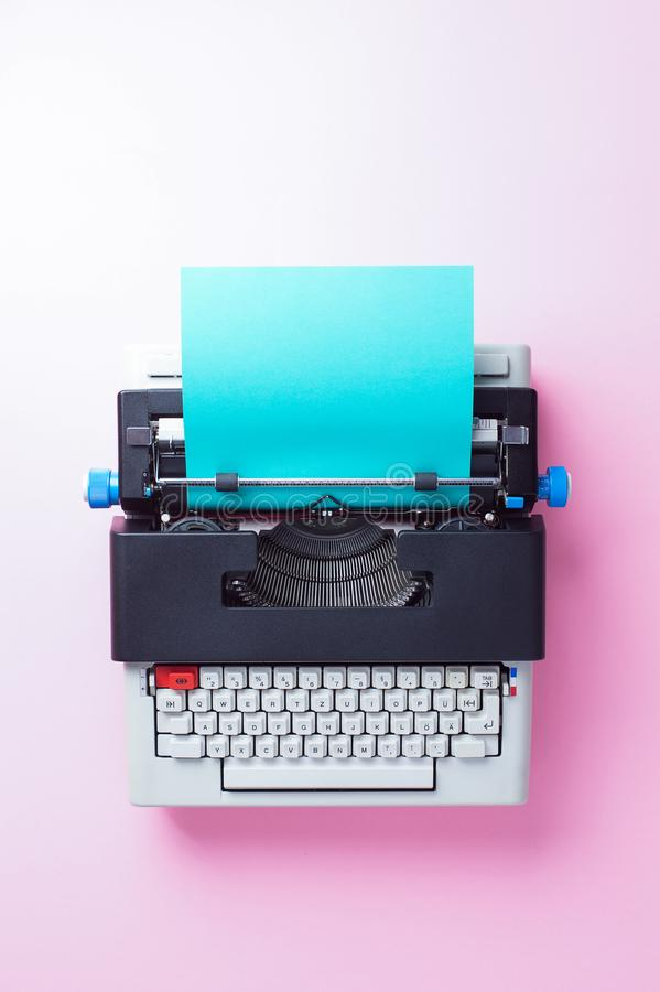 Typewriter. With blue paper over pink background, top view royalty free stock images