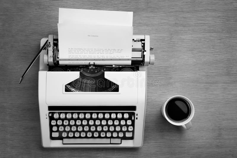 Typewriter and cofee. Typewriter with bible script on the paper and a mug of coffee stock images
