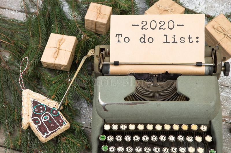 Typewriter with the inscription 2020 To do list, fir branches, gift boxes and gingerbread house. Christmas concept - Typewriter with the inscription 2020 To do stock image