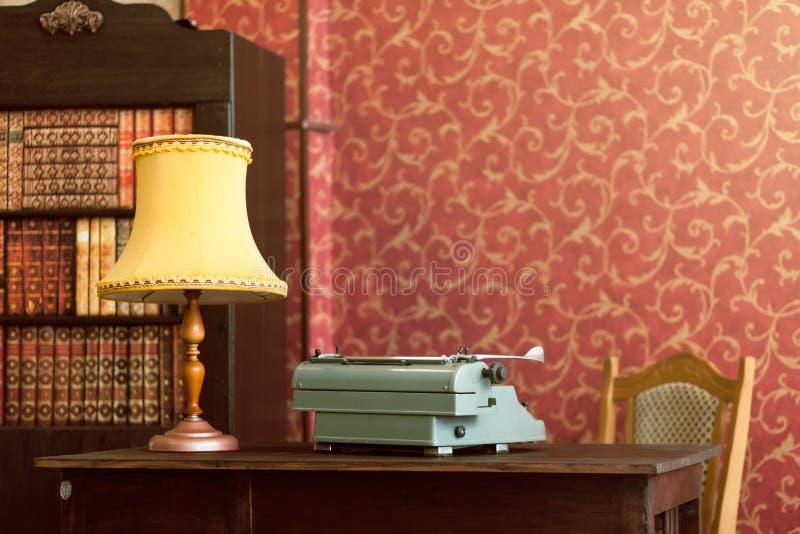 Typewriter, lamp, books stock photography