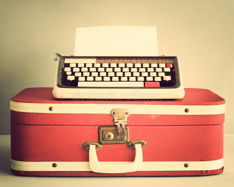 Typewriter over suitcase. Vintage typewriter over a red suitcase stock photo