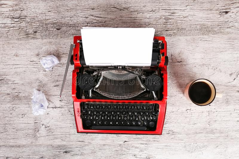 The typewriter is red with paper in it and on the table. The typewriter is red with paper in it and on a gray wooden table royalty free stock photo