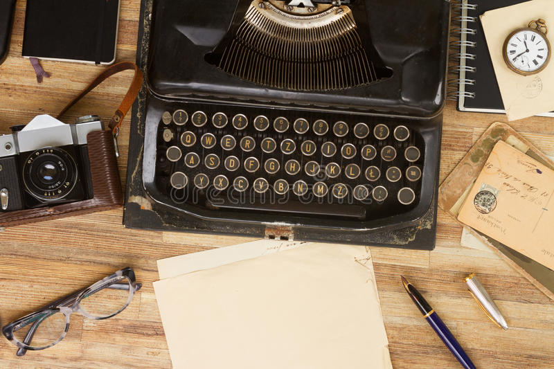 Typewriter on table. Black antique typewriter with supplies on wooden table, copy space on aged paper, top view stock images