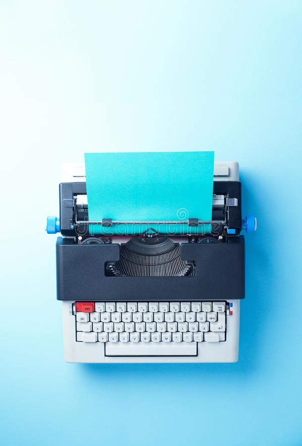 Typewriter. With blue paper over blue background, top view stock photography