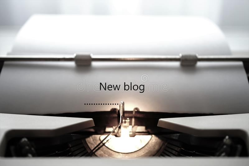 Typewriter typing the words `New blog` stock photography