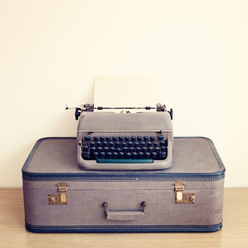 Typewriter and vintage suitcase. Grey typewriter over a vintage suitcase stock photo