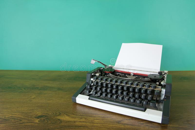 Typewriter. Vintage typewriter on wooden desk. Mint green background royalty free stock image
