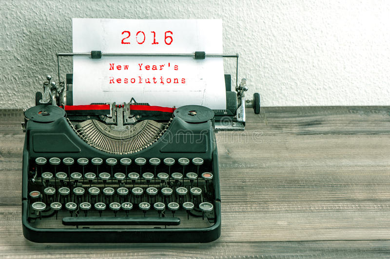 Typewriter with white paper page. New Year's Resolutions. Typewriter with white paper page on wooden table. sample text 2016 New Year's Resolutions. vintage royalty free stock images