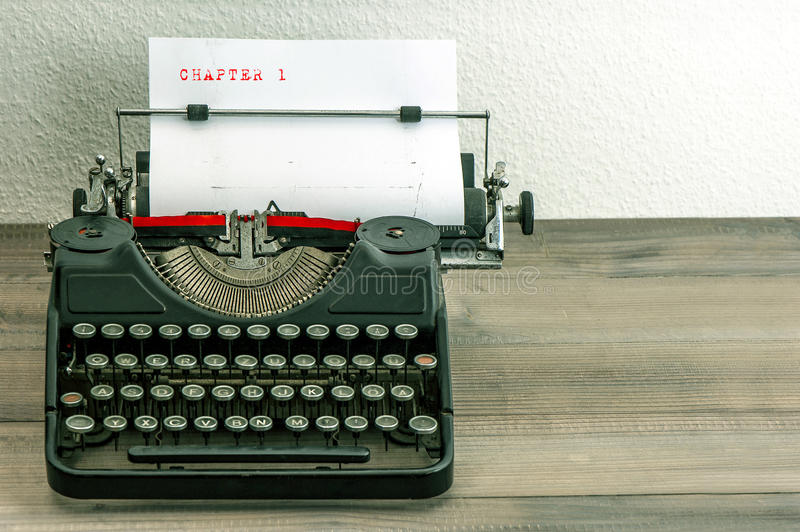 Typewriter with white paper page. On wooden table. sample text Charter 1 royalty free stock image