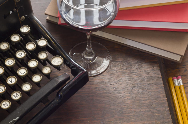 Typewriter Wine Books. Old vintage typewriter with glass of wine pencils and books in this retro creative writing and relazation themed desk top stock image