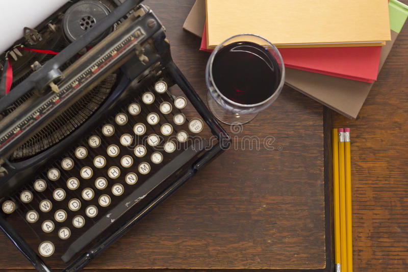 Typewriter Wine Books. Old vintage typewriter with glass of wine pencils and books in this retro creative writing and relazation themed desk top stock photo