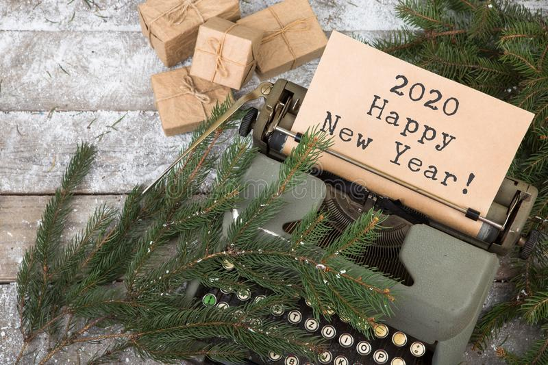 """typewriter with the words """"2020 Happy New Year!"""", gift boxes and spruce branches on a wooden table stock photo"""