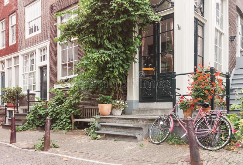 Typical Amsterdam old city street view with traditional buildings and vintage bicycle. On calm summer day, no people stock photo
