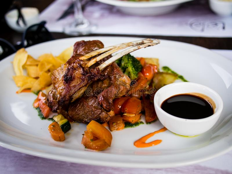 Typical Argentinean lamb chops with vegetables stock images