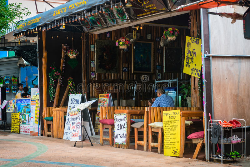Typical asian bamboo restuarant in Krabi. AO NANG, KRABI, THAILAND - 15 OCT 2014: Asian restaurant with bamboo tables and chairs with a shoe rack outdoors and royalty free stock image