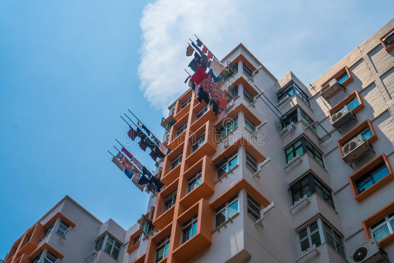 Typical Asian highrise public housing estate against blue sky. Typical Asian highrise public housing estate with air conditioners and laundry against blue sky royalty free stock image