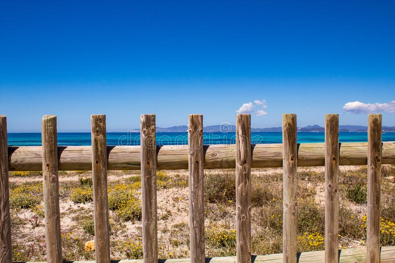 Typical balearic natural reserve wooden fence, and blue mediterranean sea on the background; Formentera Island, Spain stock photography