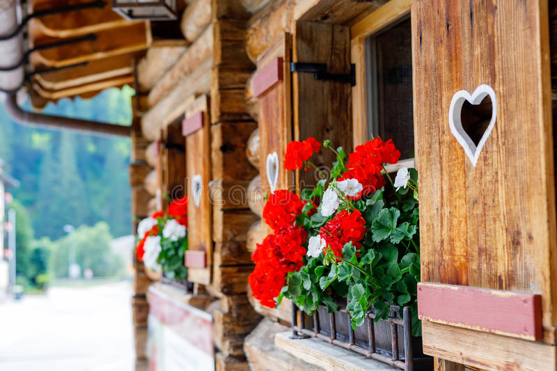 Typical bavarian or austrian wooden window with red geranium flowers on house in Austria or Germany royalty free stock photo
