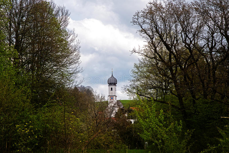 Typical Bavarian Catholic church tower with onion dome between g stock photos