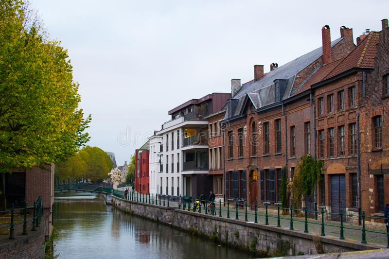 Typical belgian street in Patershol in the coastline of Lys river and a bridge at the background, with houses and trees.  stock image