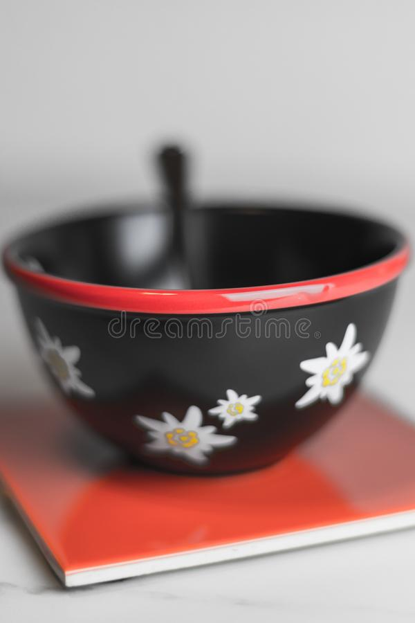 Typical black swiss cereal bowl with edelweiss on the side on a stock photo