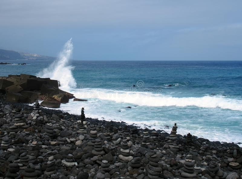Typical black volcanic beach in the tenerife with deep blue sea and a wave breaking over rocks with stacked stones. And pebbles royalty free stock photo