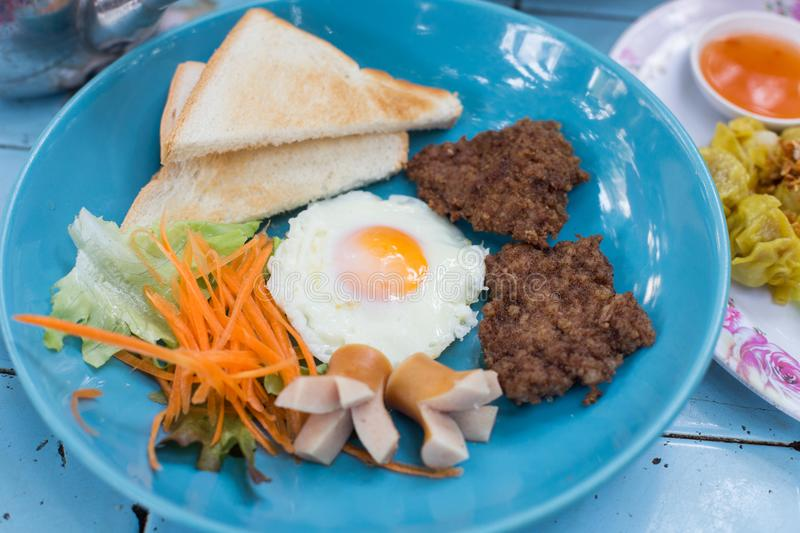 Typical breakfast with fried egg, fried pork, sausages, and toasted bread on a blue plate and blue table royalty free stock images