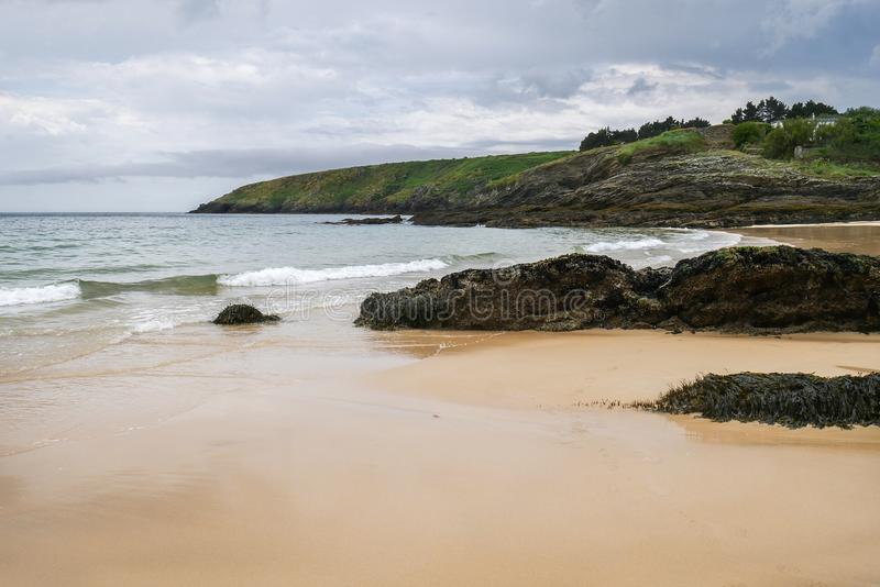 Typical brittany landscape with lonely beach with rocks covered with algae and seaweed and cloudy sky in the background stock photo