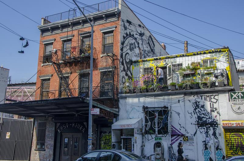 Typical Brooklyn building on 6th St in the Williamsburg neighborhood of New York City, USA. Man adjusting a bicycle on a terrace stock photos
