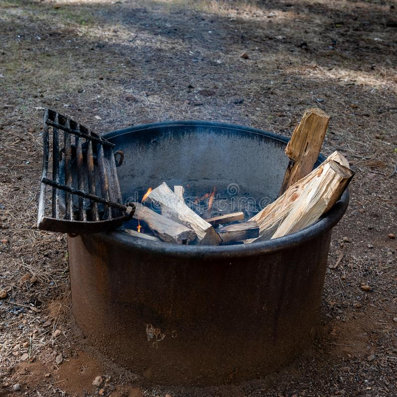 Typical campground metal fire ring. Typical metal fire ring at a California State Park campground, with wood inside and fire burning, on the ground and viewed stock images