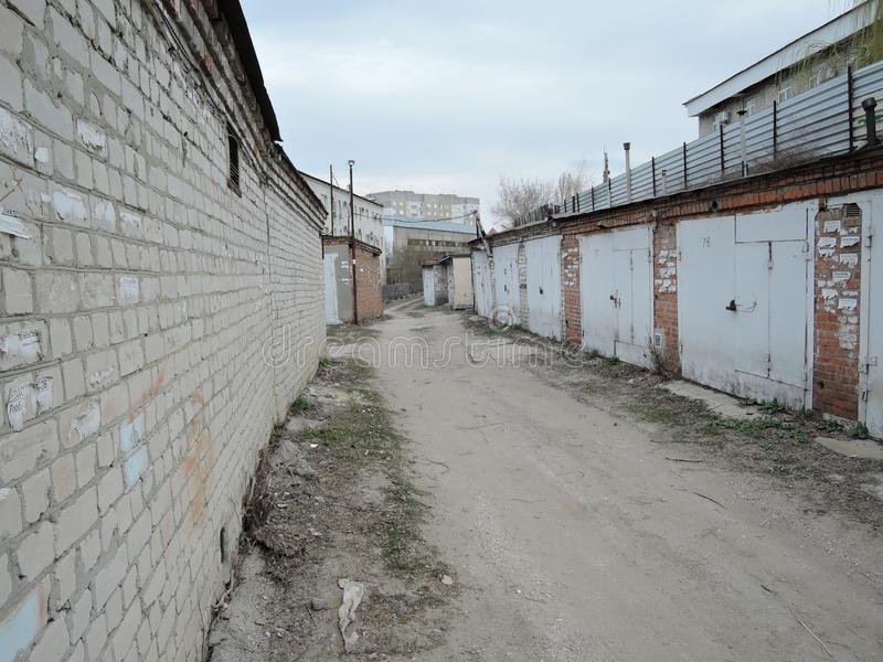 Typical complex of old concrete garages with closed metallic doors in Russia. driveway road through garages with royalty free stock images