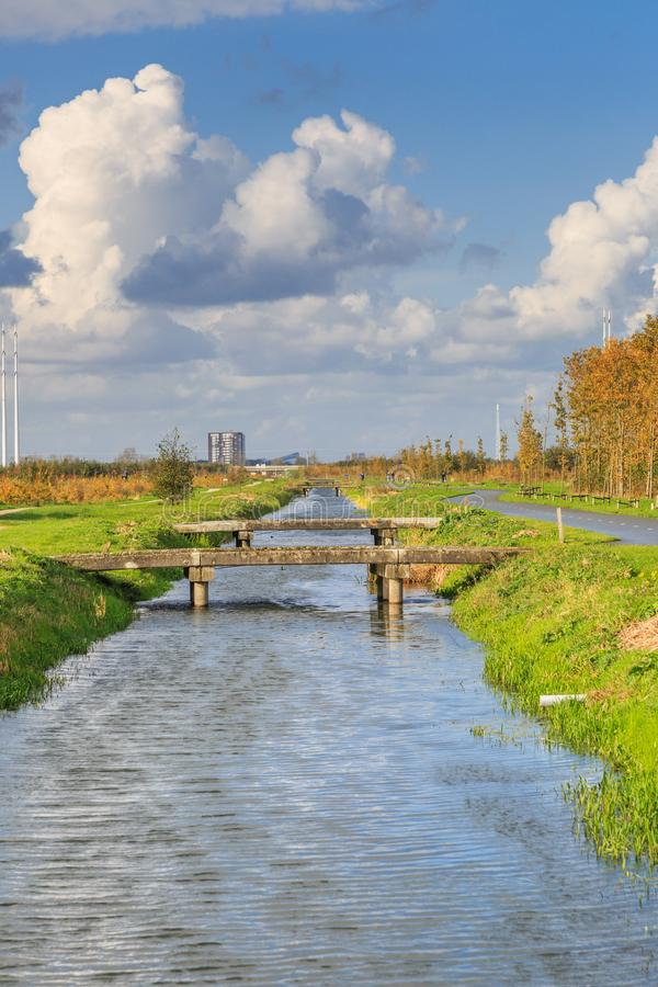 Typical Dutch flat polder landscape with cana and bridges. Typical Dutch flat polder landscape with ponds, Reed belt and canals with old and new bridges against stock photography