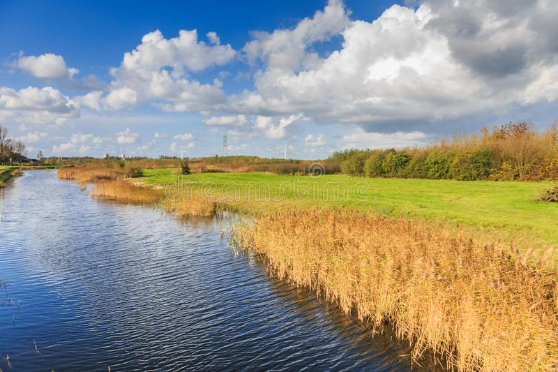Typical Dutch flat polder landscape. With ponds, Reed belt and canals with old and new bridges against blue sky with scattered clouds stock photos