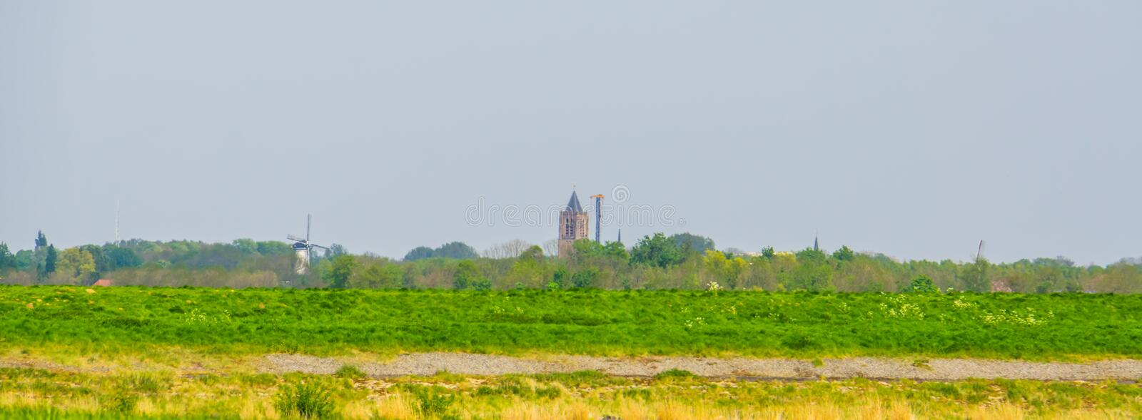 Typical dutch green landscape with a church and windmills, skyline Tholen, Zeeland, The netherlands. A typical dutch green landscape with a church and windmills stock photo