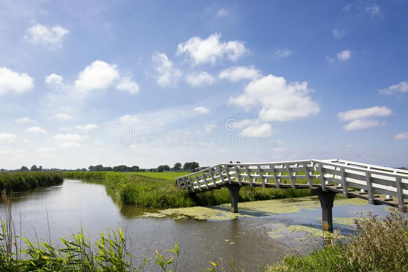 Typical Dutch landscape with green meadows, grass, bridge, water, blue sky and clouds. Typical flat Dutch landscape with green meadows, grass, bridge, flat water royalty free stock photos