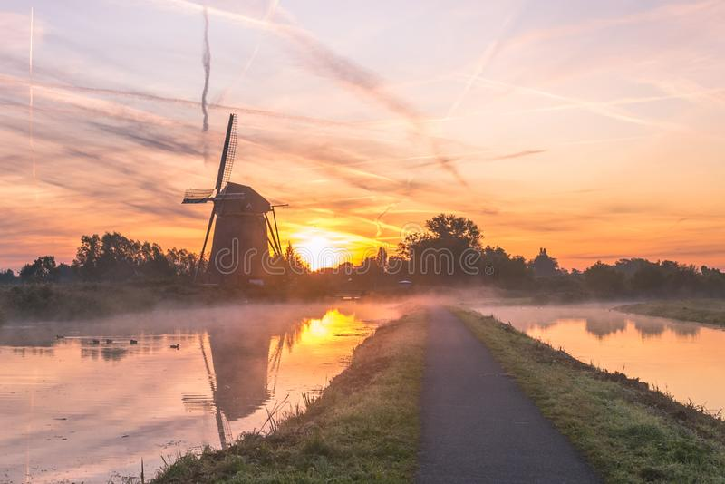 Typical dutch landscape image with windmill and fog over the water at sunrise stock image