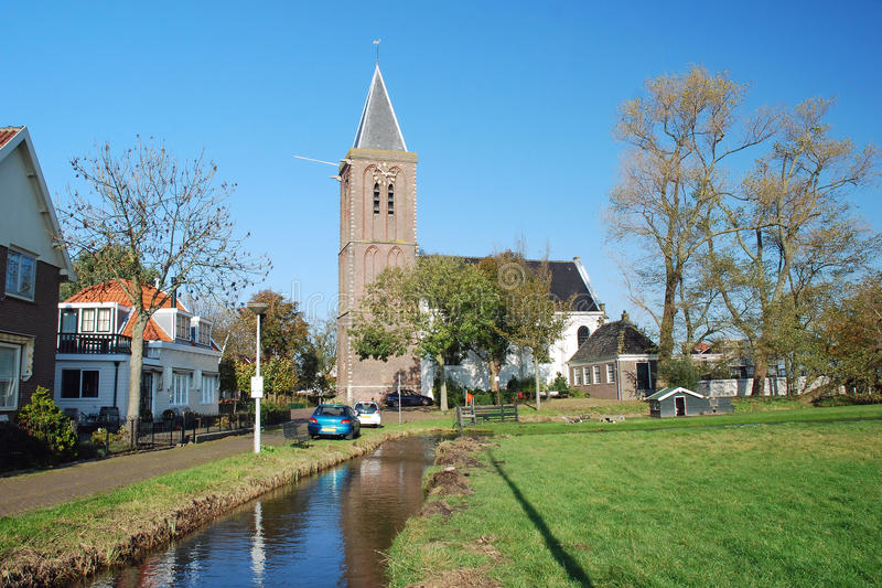 Typical Dutch village- with church - wooden houses. Typical Dutch agraric village Zunderdorp with wooden houses and Dutch Reformed church in the rural part of royalty free stock photo