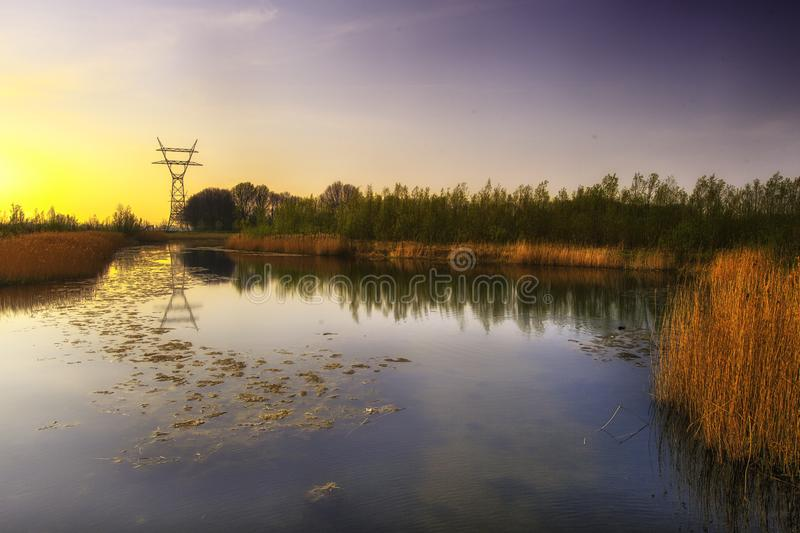 Dutch water landscape. A typical Dutch water landscape with a power pylon showing the encroachment of civilisation and industries on nature royalty free stock images