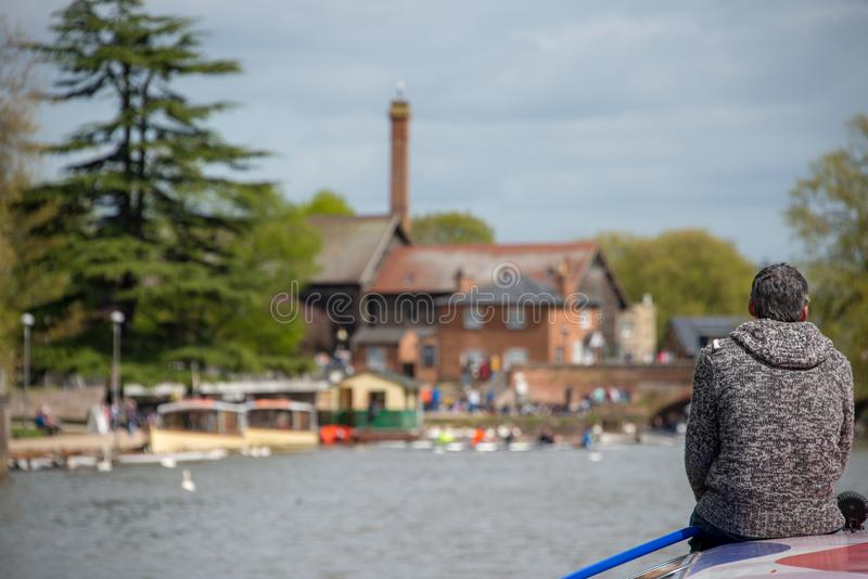 Typical English river scene with beautiful natural light and old buildings with chimney. Retired lonely man sat on bow of boat wearing grey jumper with gray hair royalty free stock photos