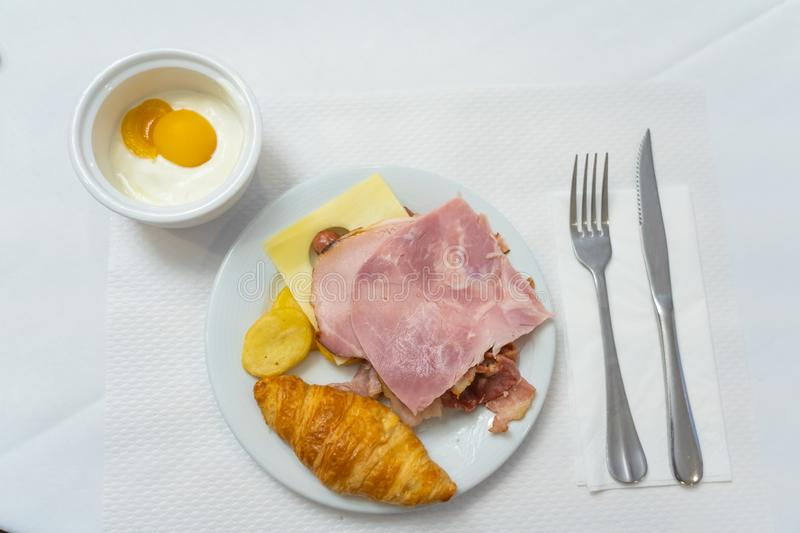 Typical European breakfast with cheese ham croissant and fruit yogurt stock photo
