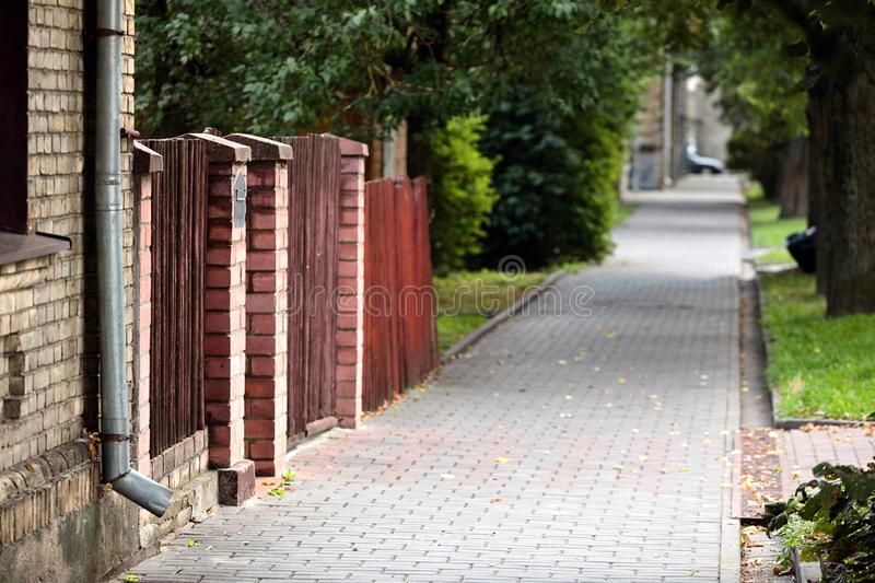 Typical European summer cityscape of old street with paving slabs, brick-walled house, gate and alley in Grodno stock photography